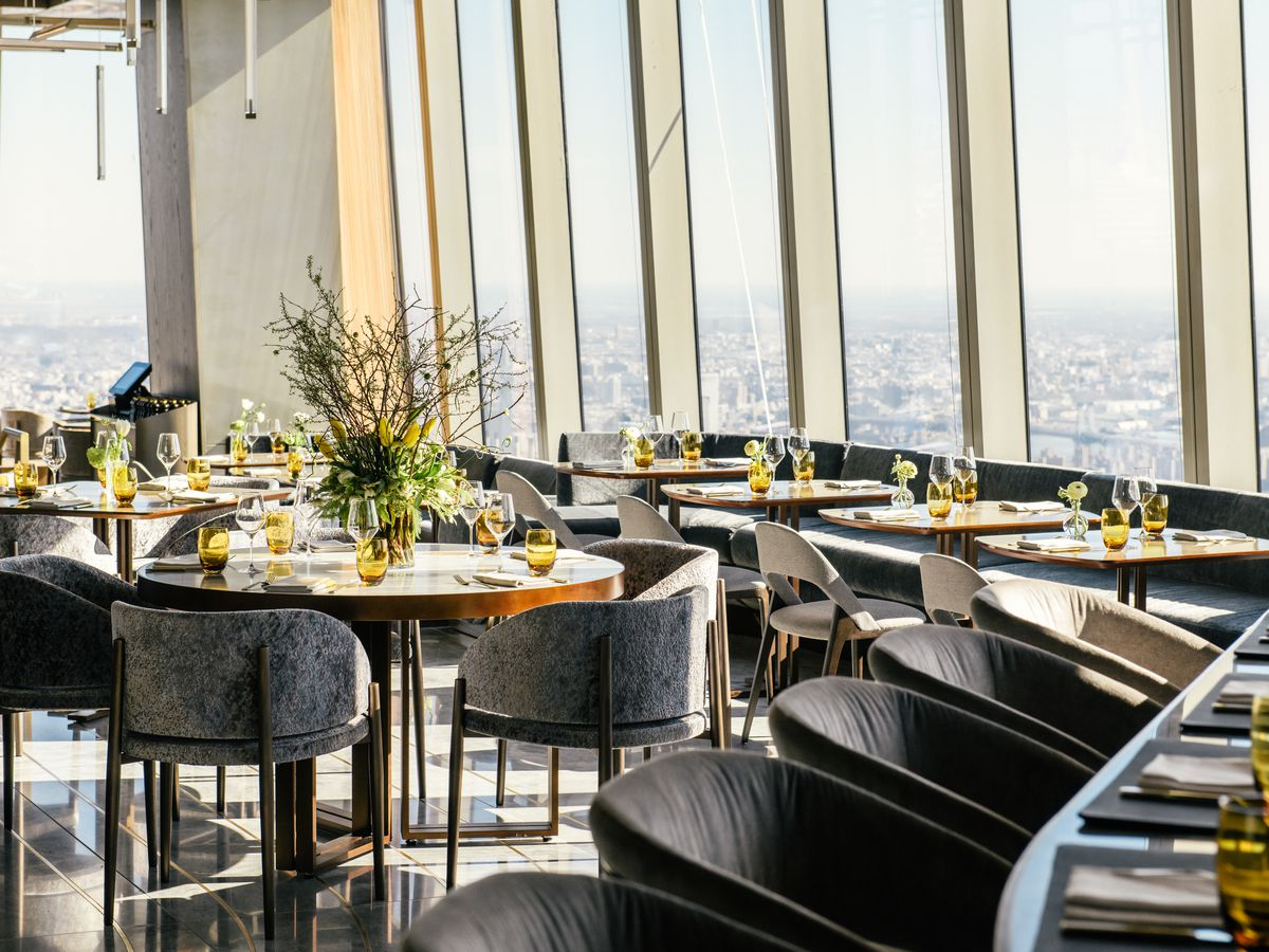 Tables and chairs are arranged in an ornate dining room set high above ground level, with distant views of a city skyline visible through a window