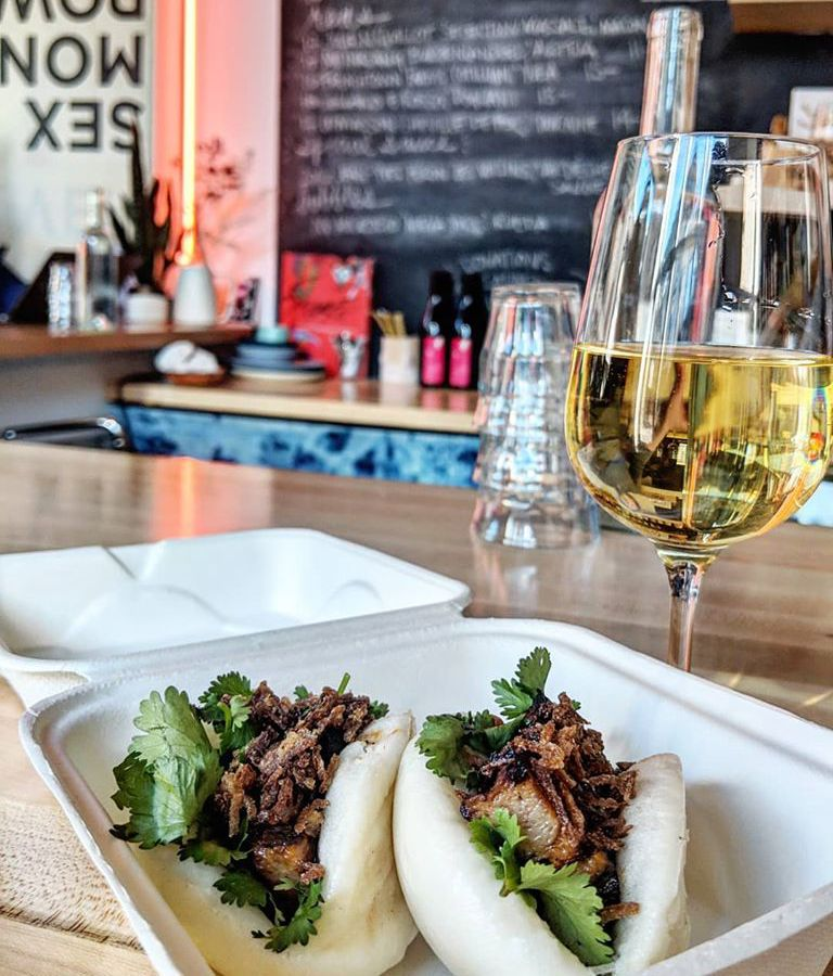 Two soft buns stuffed with pork belly and greens sit on a plate on a light wooden bar, with a glass of white wine visible in the background
