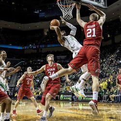 Oregon forward Mikyle McIntosh (22), shoots against Utah forward Tyler Rawson (21) during the first half in an NCAA college basketball game Friday, Dec. 29, 2017, in Eugene, Ore. (AP Photo/Thomas Boyd)