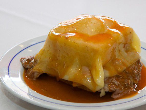 Melted cheese and sauce covers a mound of other ingredients on a white plate where sauce and meat can be seen pooling