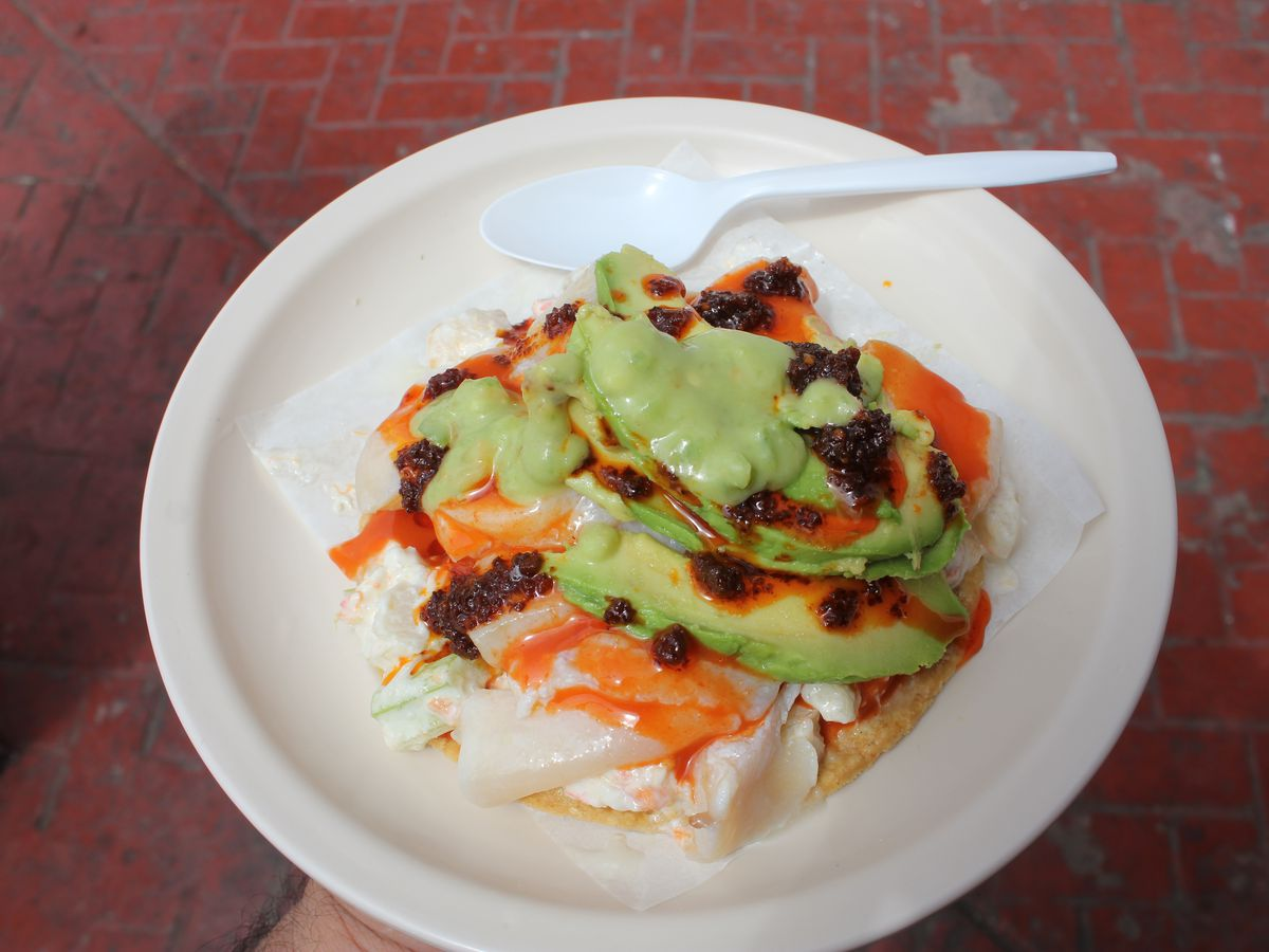 A tostada topped with slices of crab and clam, as well as avocado and red sauce spotted with clumps of ground chiles, on a paper plate beside a plastic spoon