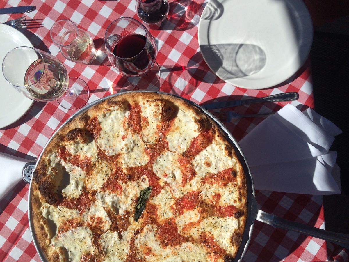 A pizza with mozzarella and red sauce sits on top of a red-checkered tablecloth, with glasses of wine.