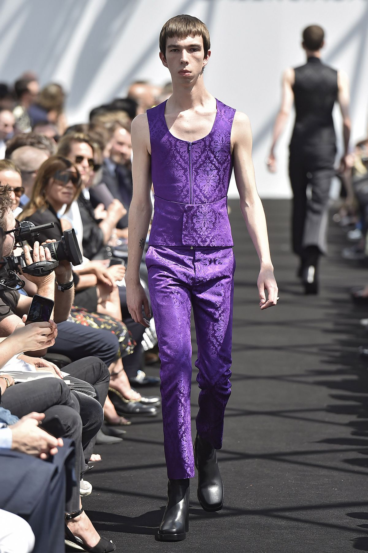 A model walks Balenciaga's spring 2017 menswear show wearing a bright purple vest and trousers.