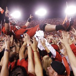 Utah fans storm the field and hoist Utah Utes quarterback Jon Hays (9) after the Utes beat BYU in Salt Lake City  Sunday, Sept. 16, 2012. in Salt Lake City  Sunday, Sept. 16, 2012.