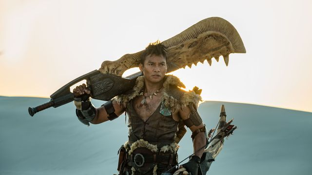 Tony Jaa, dressed in leather and fur, holds a giant, serrated sword over his shoulders in a desert.