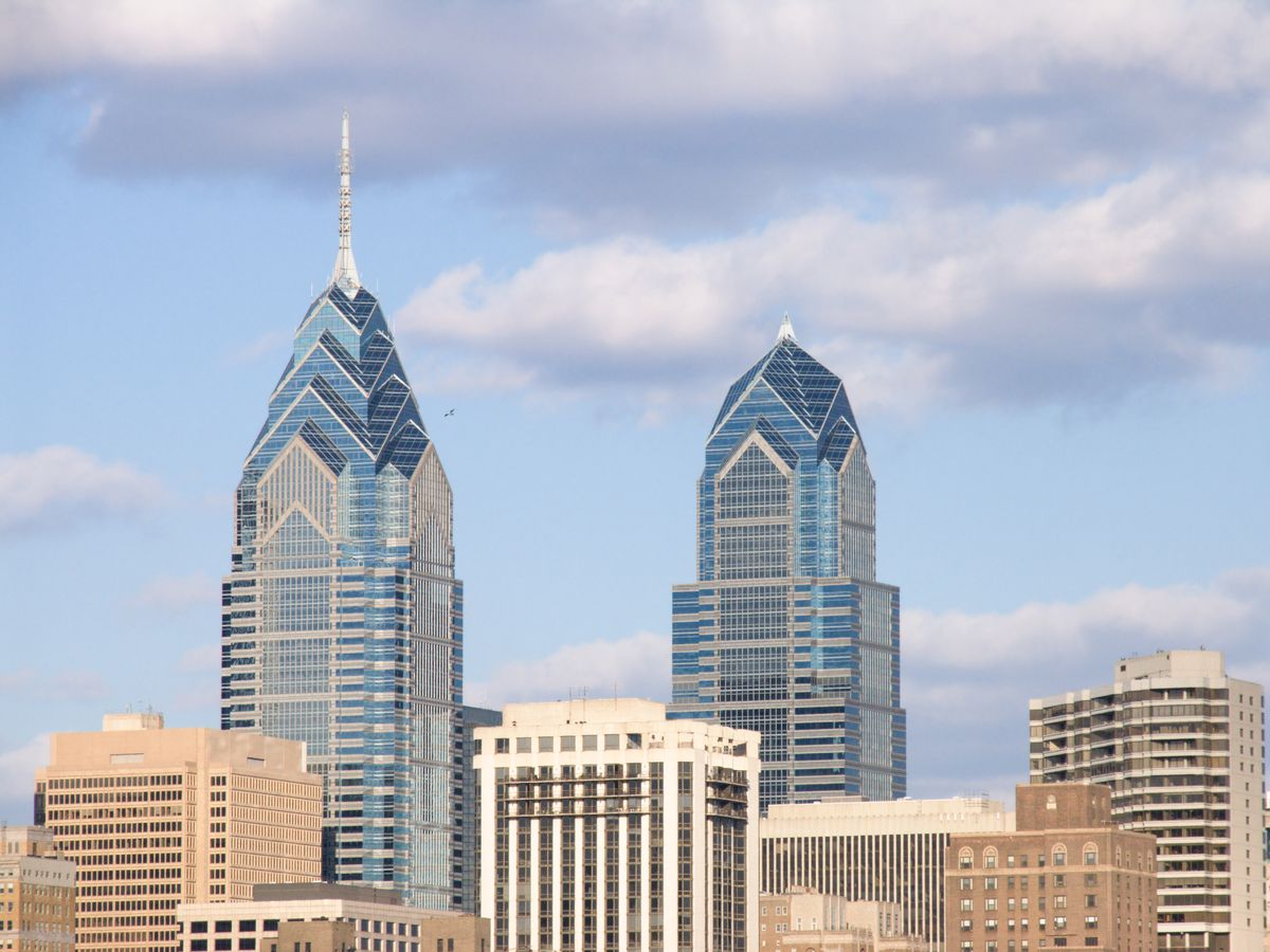 The top of the One Liberty Place building in Philadelphia. The facade is glass and the top is geometric in structure.