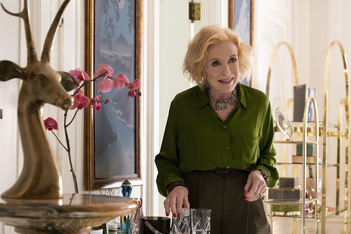 An older woman wearing an emerald green shirt is making a drink. Her room is furnished with a gold shelf, flowers, a wood deer sculpture, and landscape paintings.