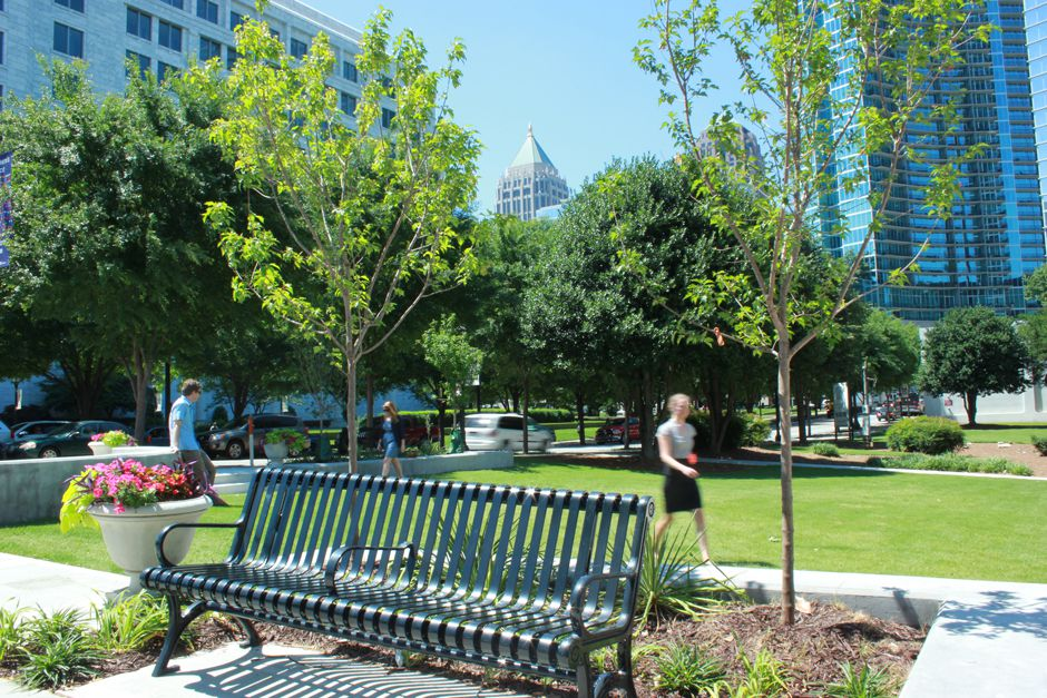 A small public park with green space and people walking around it.