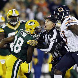 Field judge George Trout gets between Green Bay Packers' Randall Cobb (18) and Chicago Bears' J.T. Thomas (97) during the first half of an NFL football game Thursday, Sept. 13, 2012, in Green Bay, Wis.