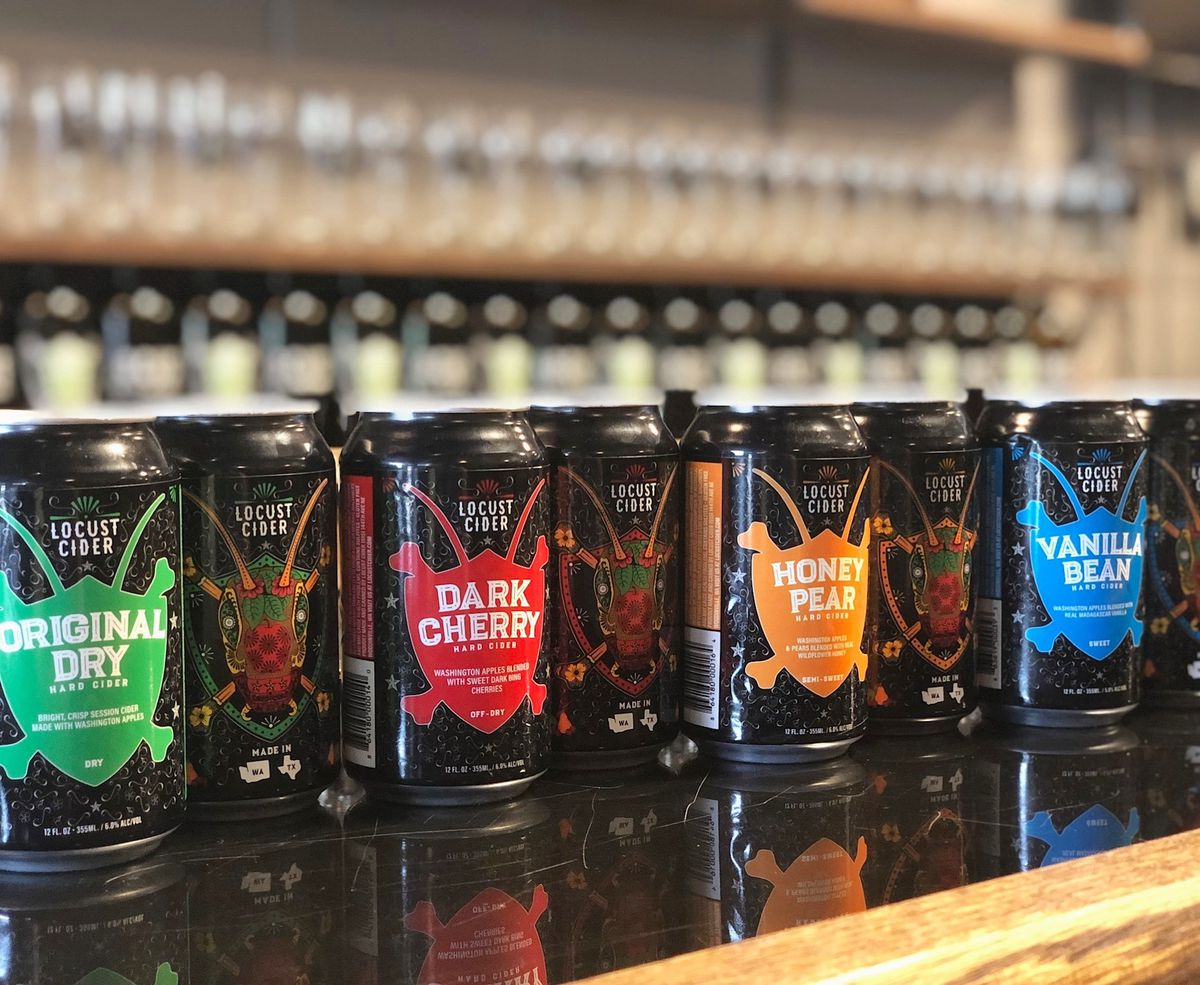 A line of Locust Cider cans sitting on a bar