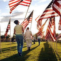 """Volunteers place flags Wednesday in the """"healing field"""" at Sandy City Hall \\\\— one for each victim of the 2001 terrorist attacks."""