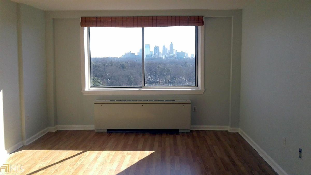 A white living room with a big window looking out on a city beyond.