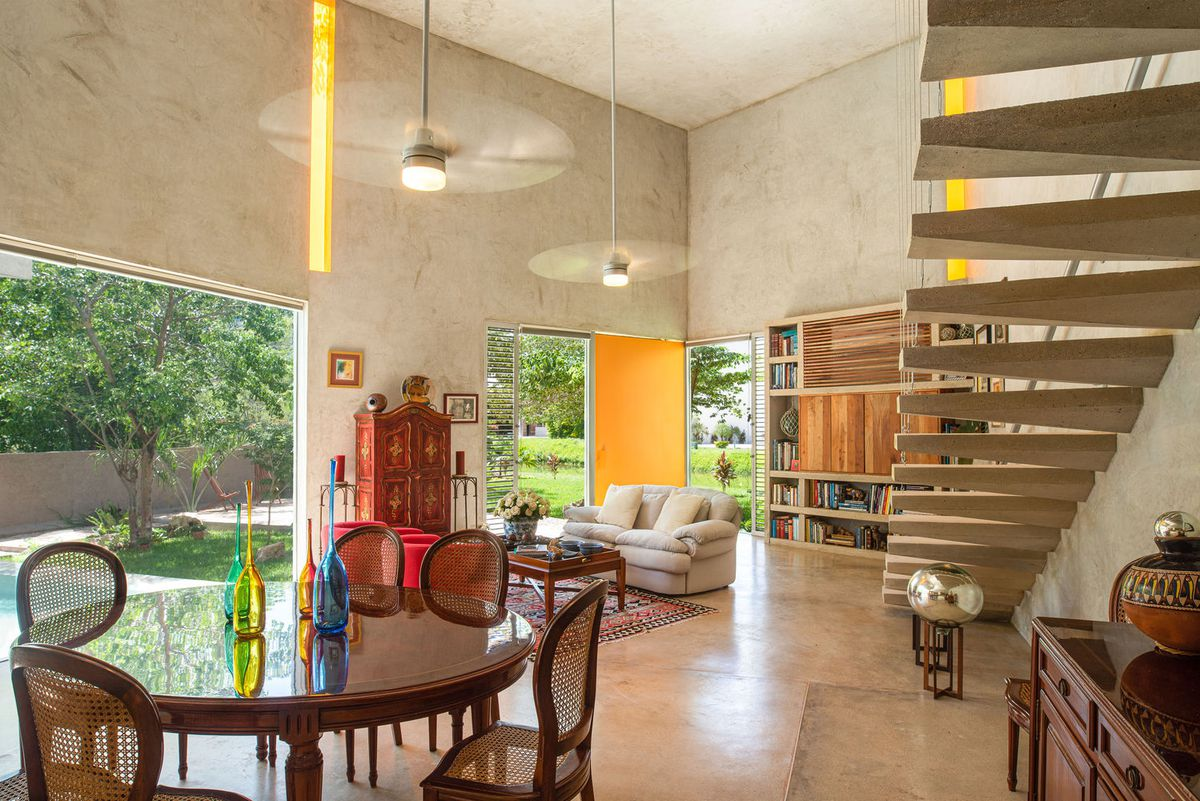 An open living room has high ceilings, a floating staircase, and a bright yellow door.