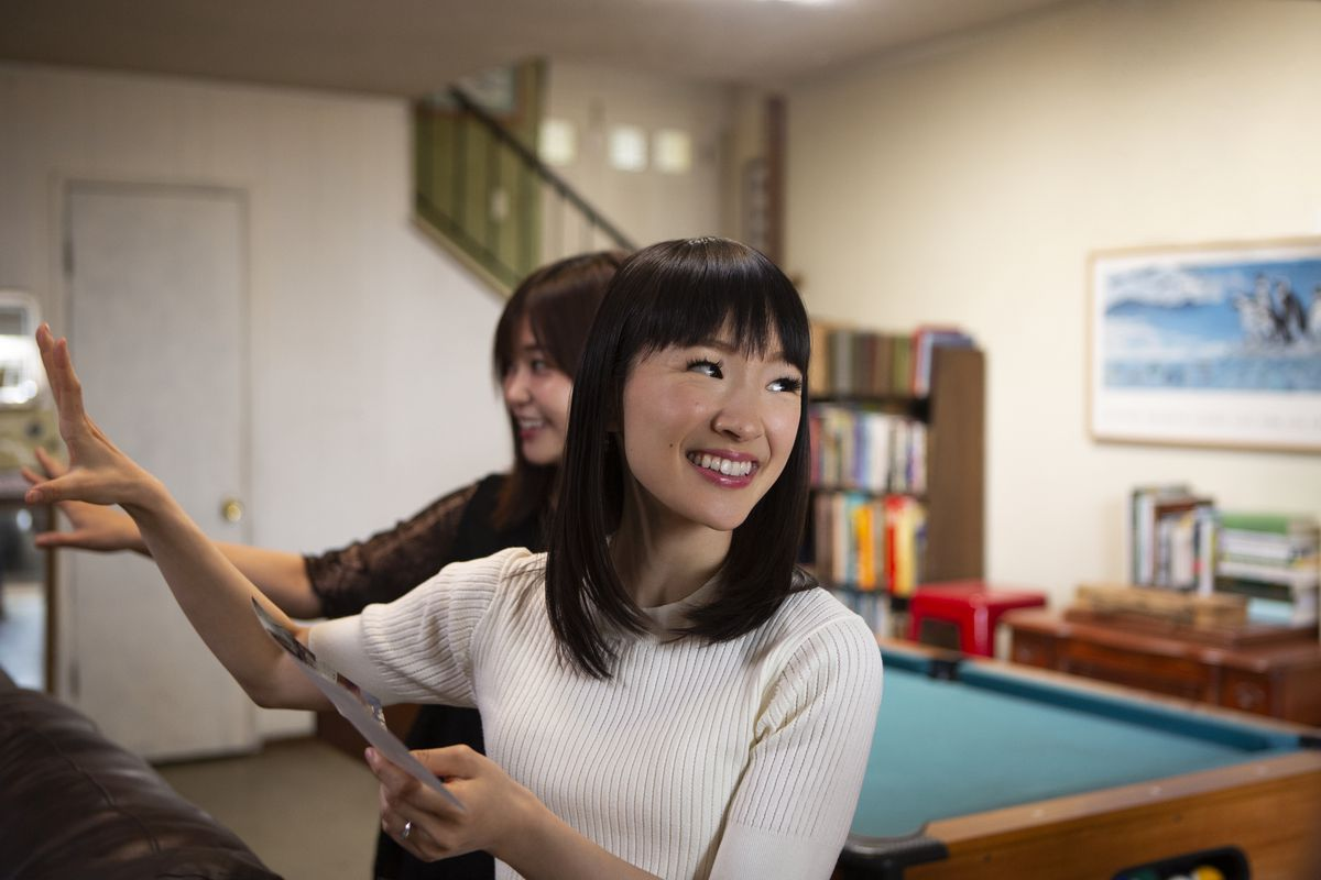 Marie Kondo smiles in front a pool table.