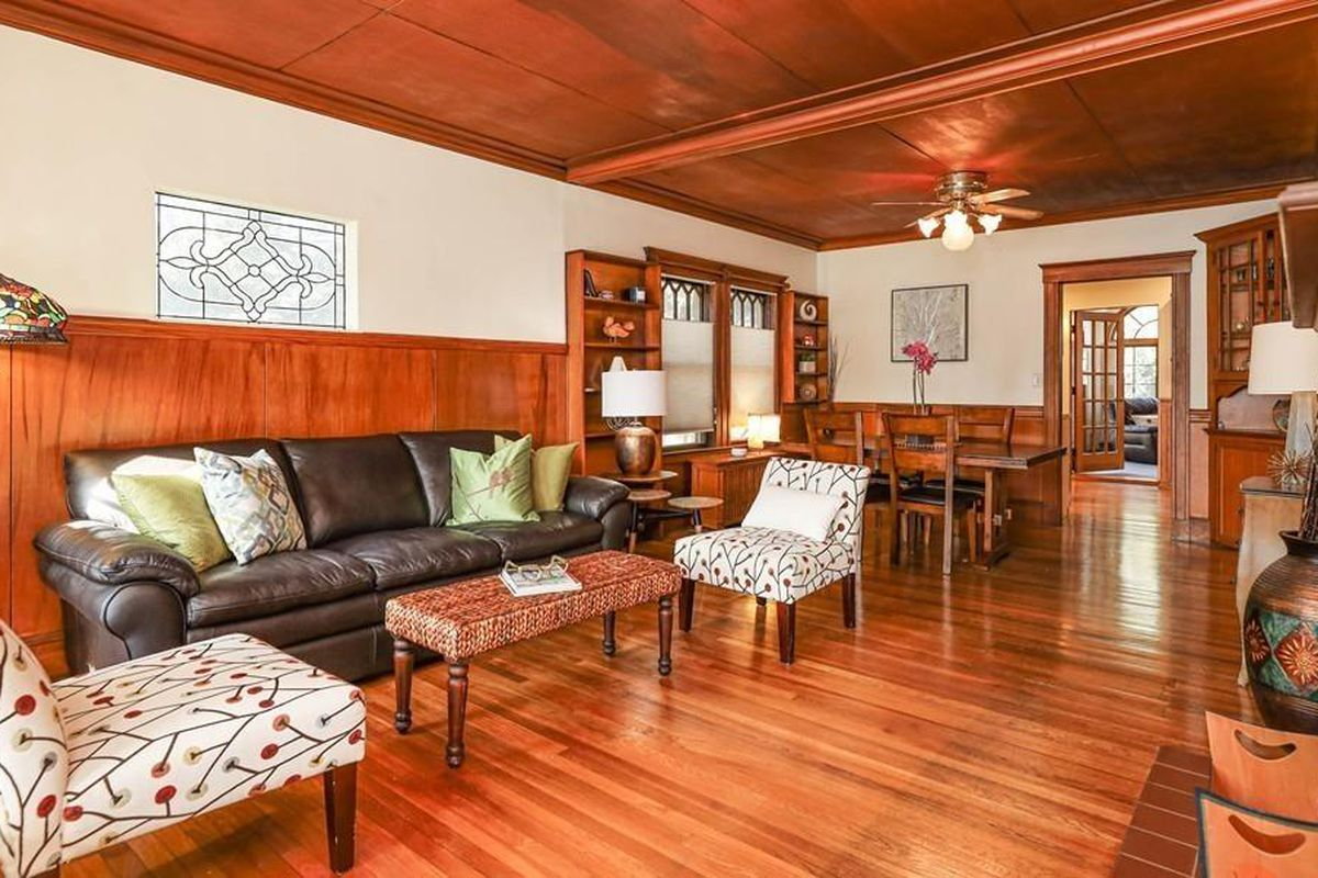 A long, spacious living room with lots of wood and furniture.