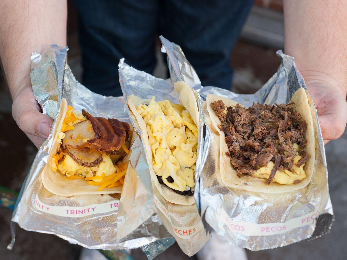 HomeState's breakfast tacos, held open inside two hands in the sun.