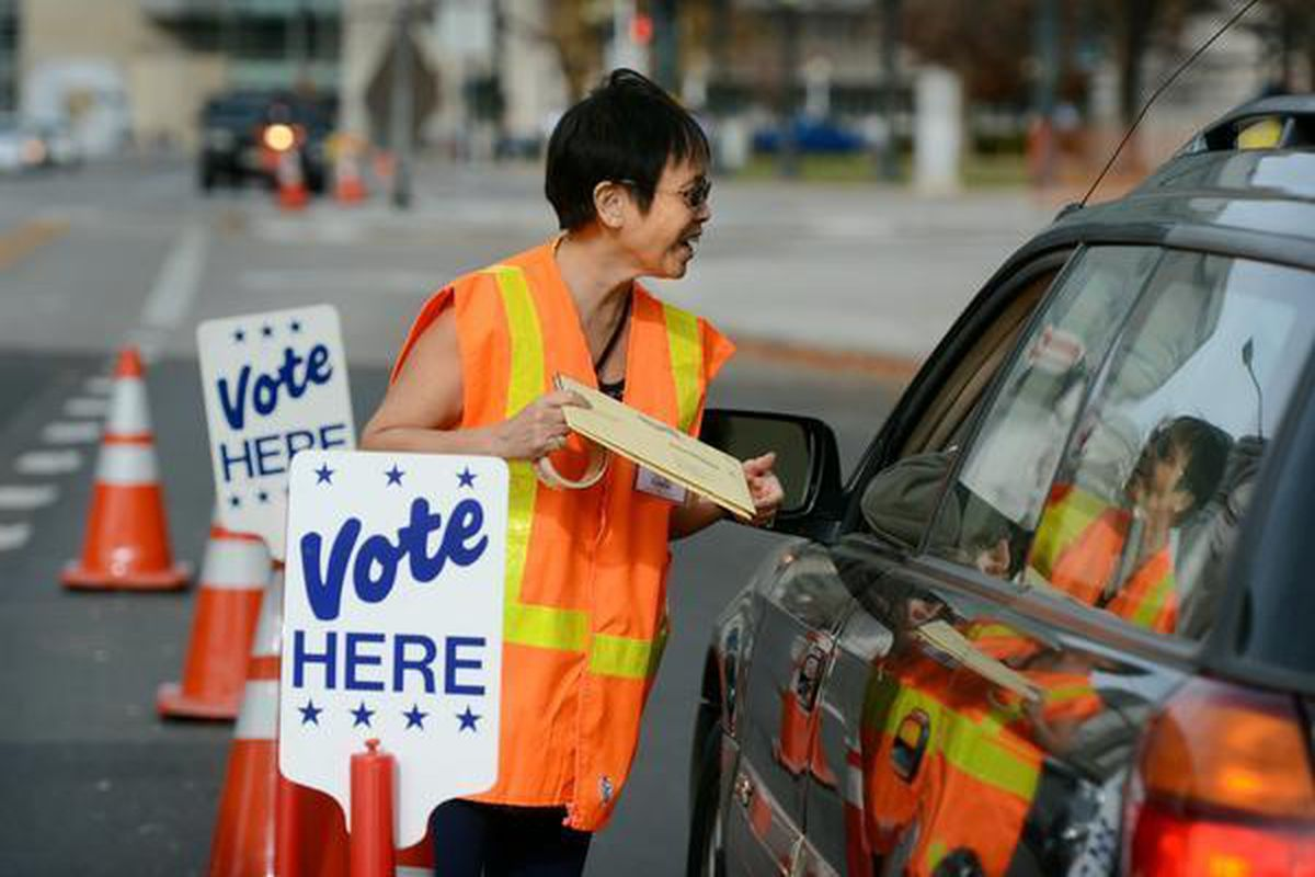 Election judge Josie Flanagan takes ballots from a voter at the drive-through ballot drop-off outside the Denver Elections Division.