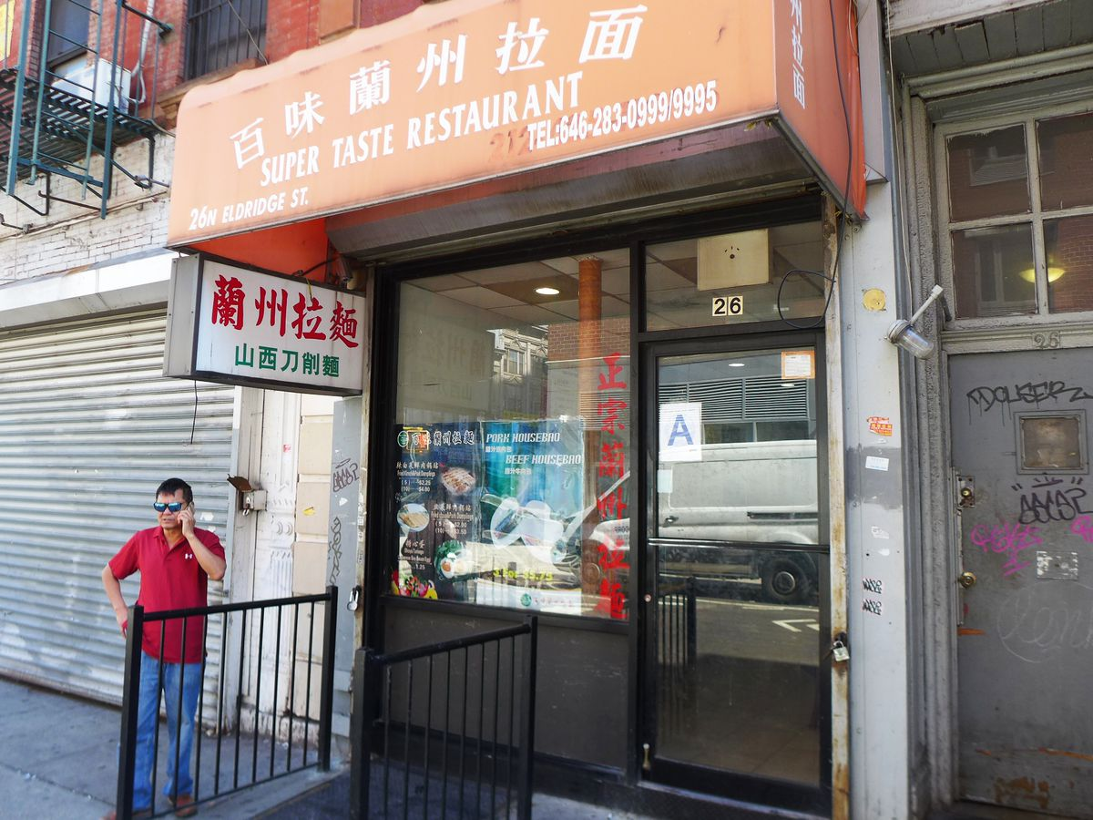 A small storefront with glass windows and a red awning.