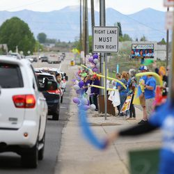 Teachers at FarrWest Elementary in Farr West, Weber County, line the street in front of the school and wave scarves at students driving past with their parents on the last day of classes on Friday, May 15, 2020.