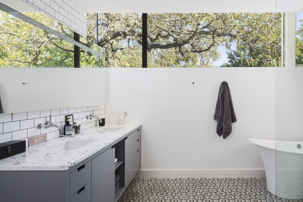 Master bathroom with a grey vanity, pattern floor tile, a bathtub, glass shower, and huge window with views of the trees outside.