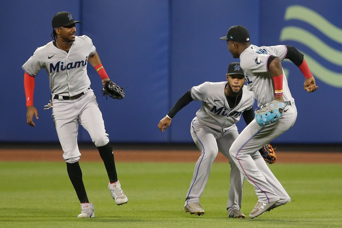 Miami Marlins right fielder Jesus Sanchez (76) and center fielder Bryan De La Cruz (77) and left fielder Lewis Brinson (25) celebrate after defeating the New York Mets at Citi Field.