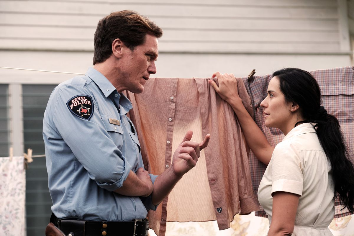A sheriff and a woman hanging laundry stand having a conversation.