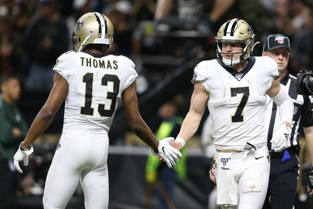 New Orleans Saints quarterback Taysom Hill (7) celebrates with wide receiver Michael Thomas (13) after scoring a touchdown against the Minnesota Vikings during the fourth quarter of a NFC Wild Card playoff football game at the Mercedes-Benz Superdome.