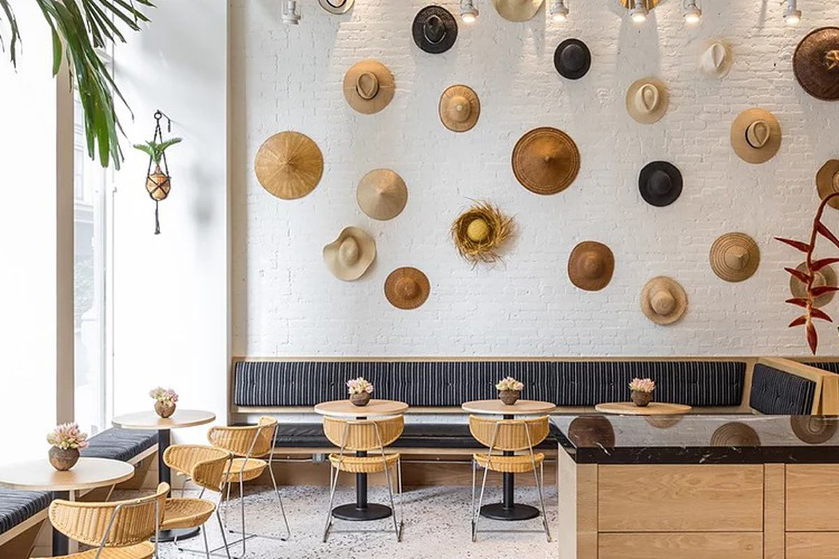 A bright white restaurant interior features palm trees and a wall of hanging beachy hats.