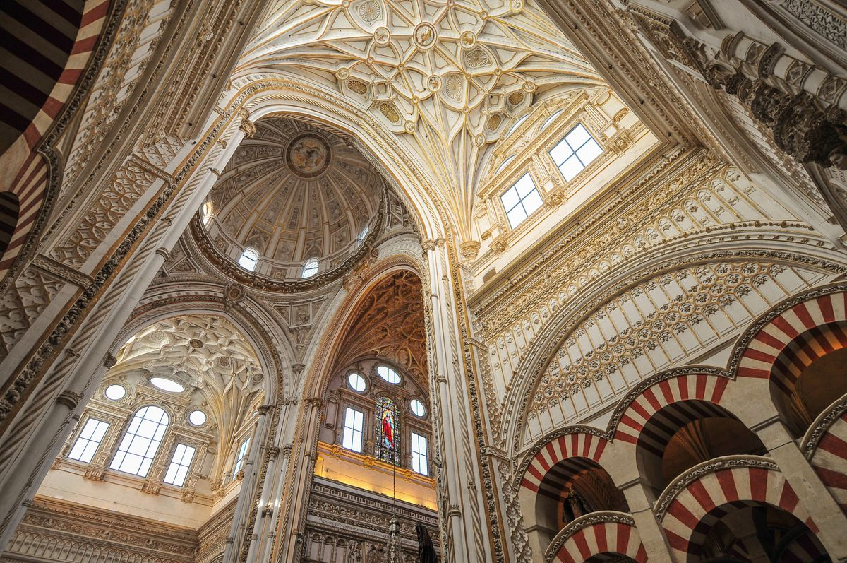 """The interior of <span data-author=""""843"""">The Mosque-Cathedral of Córdoba in Spain. The high arched ceiling is ornately decorated. There are red and white columns and arches on the lower level. </span>"""