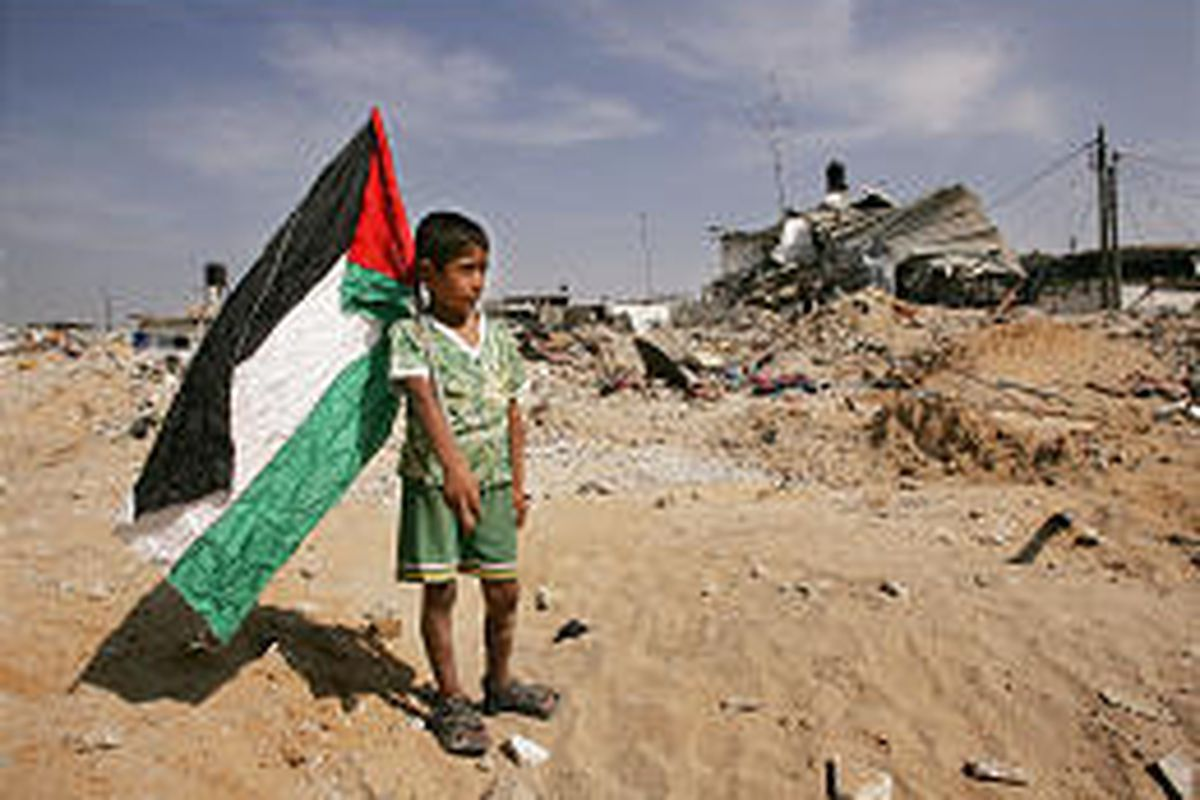 A Palestinian boy carries a flag through rubble in the Jabaliya refugee camp, northern Gaza Strip. Israel withdrew forces from the area Friday.