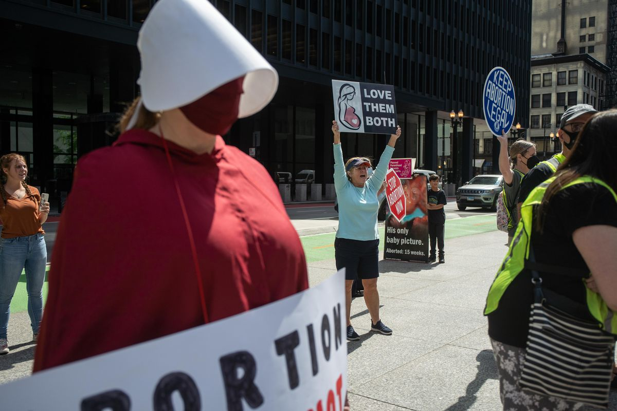 """A member of the Illinois Handmaids holds a sign as Rita Sweeney, a member of Pro-Life Action League, yells at attendees during the """"Bans Off My Body"""" rally Friday afternoon at Federal Plaza in the Loop."""