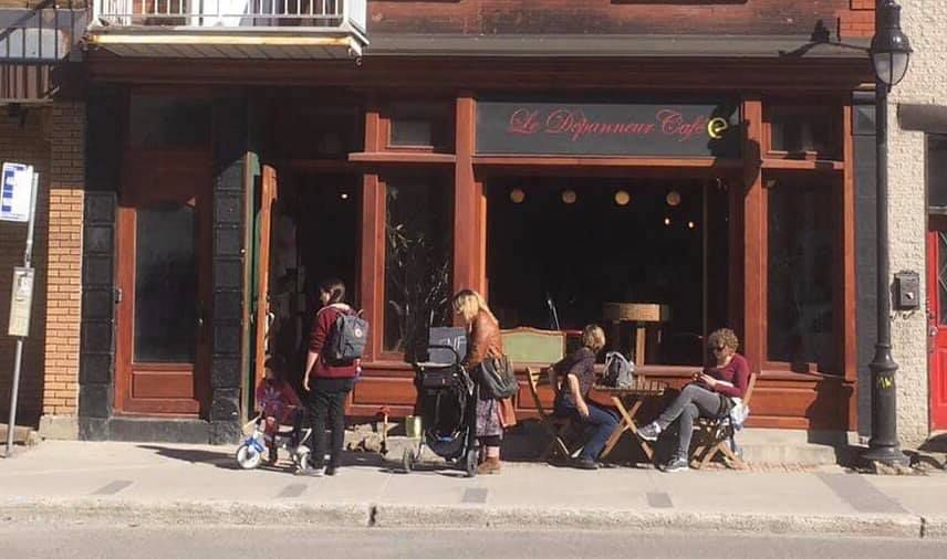 The exterior of the café, with two woman with strollers and two men sitting at a table.