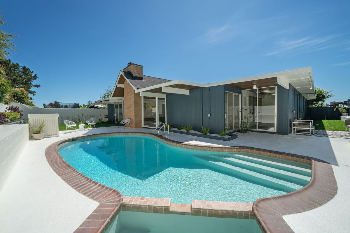 A kidney-shaped pool on a sunny day in front of the rear of the home.