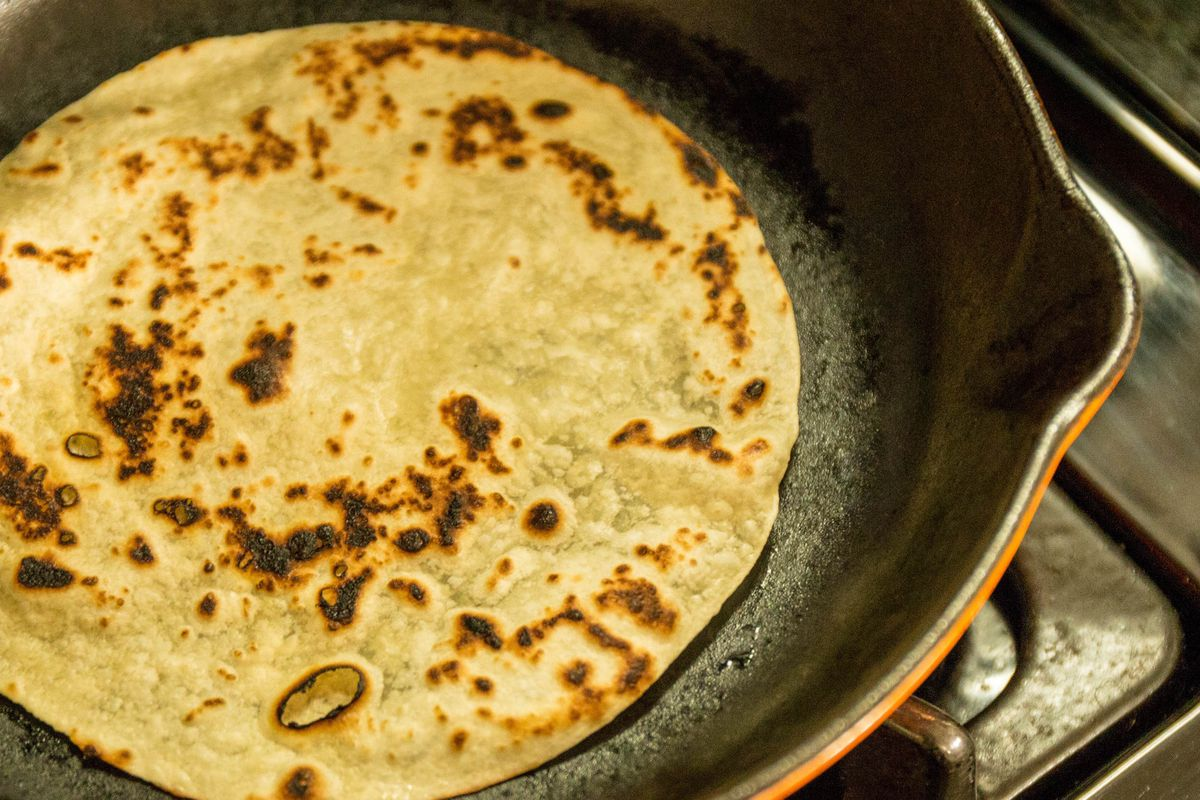 Close-up view of a well-blistered flour tortilla in a cast iron skillet