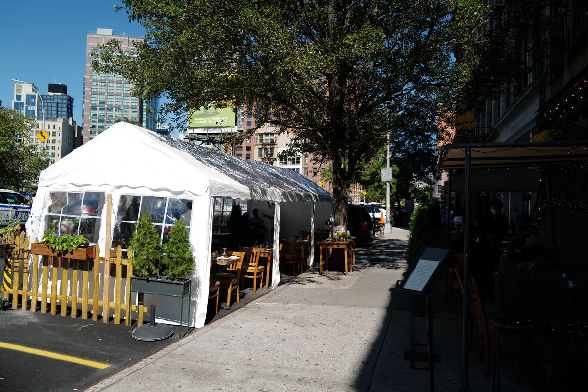 A view of a white tent with tables inside it and the tent is covered on three sides
