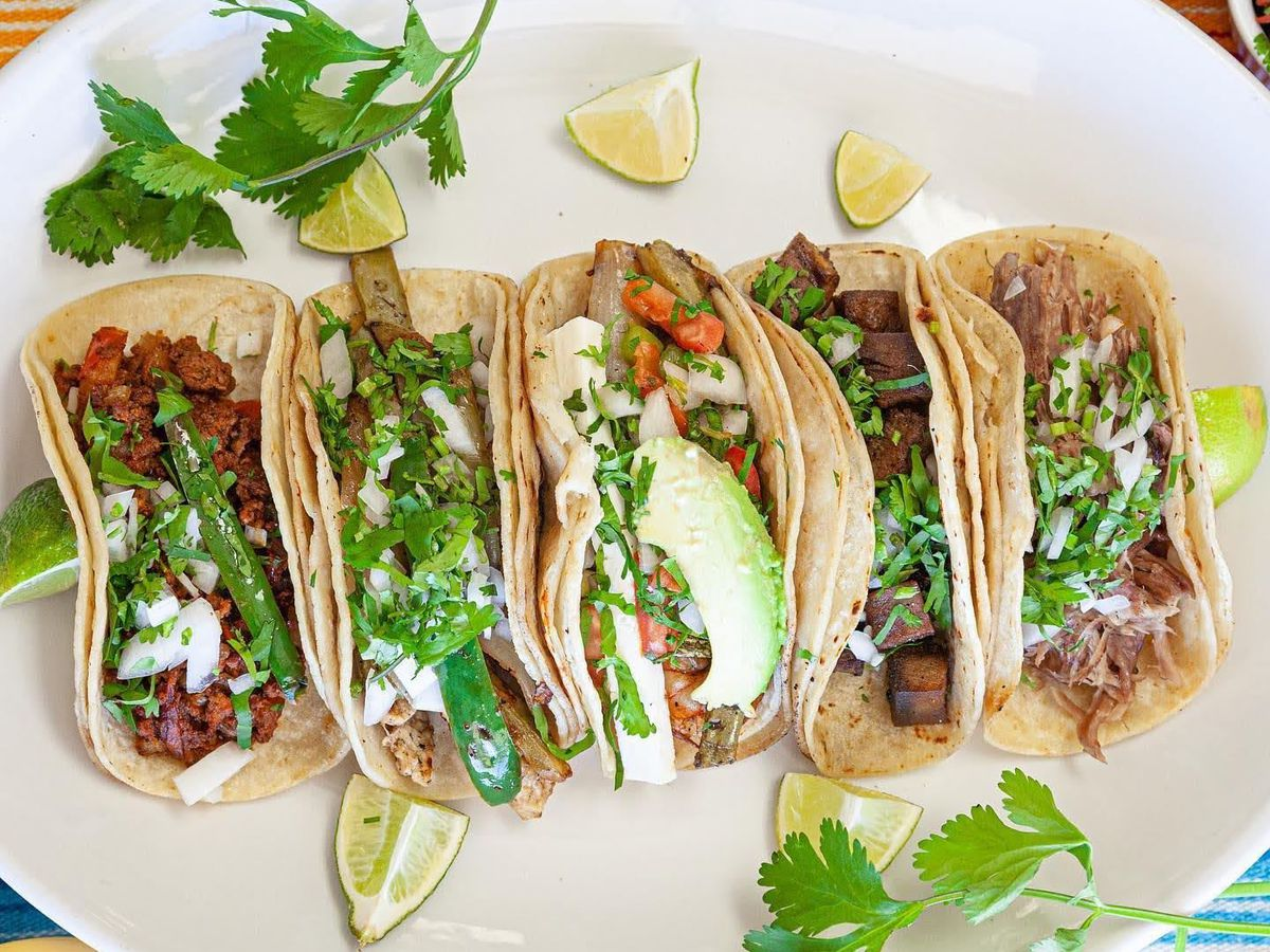 A serving plate of tacos, some full of meat, others with vegetables, peppers, and herbs, along with lime wedges