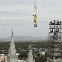 Crews watch after the Angel Moroni statue is removed from atop the Salt Lake Temple of The Church of Jesus Christ of Latter-day Saints during renovation in Salt Lake City on Monday, May 18, 2020.