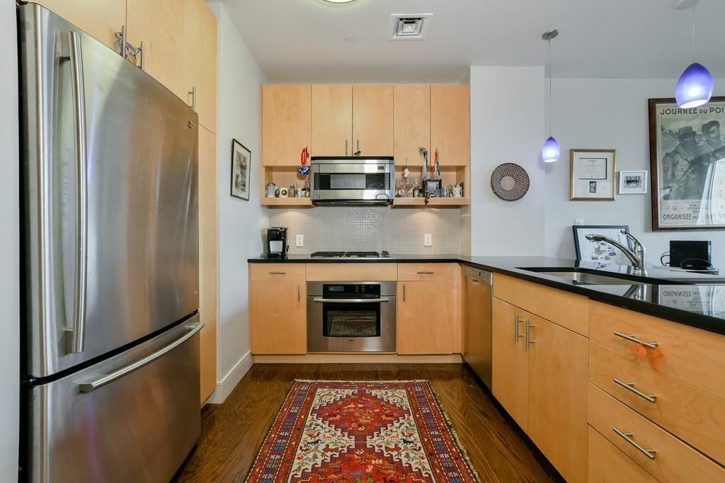 A kitchen with an L-shaped counter and a large fridge.