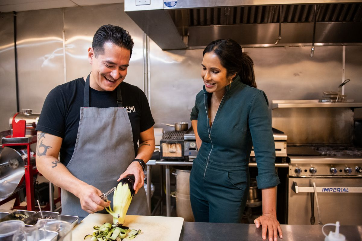 Padma Lakshmi watches as chef Emiliano Marentes peels an ear of corn in a restaurant kitchen