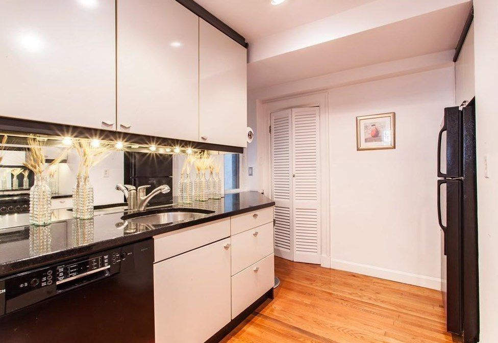A kitchen with a counter facing a fridge.