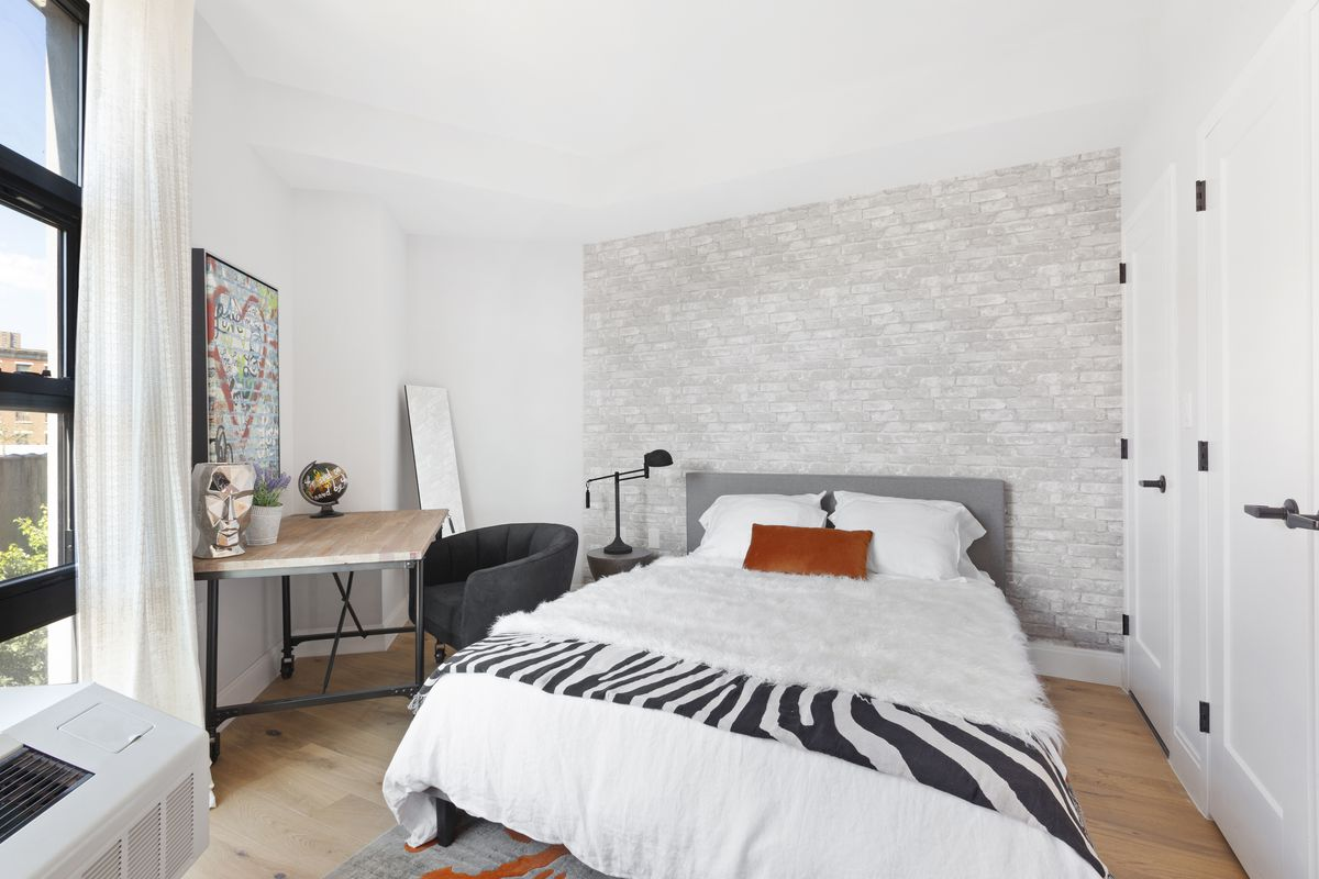 A bedroom with a large bed, white walls, a large window, and hardwood floors.