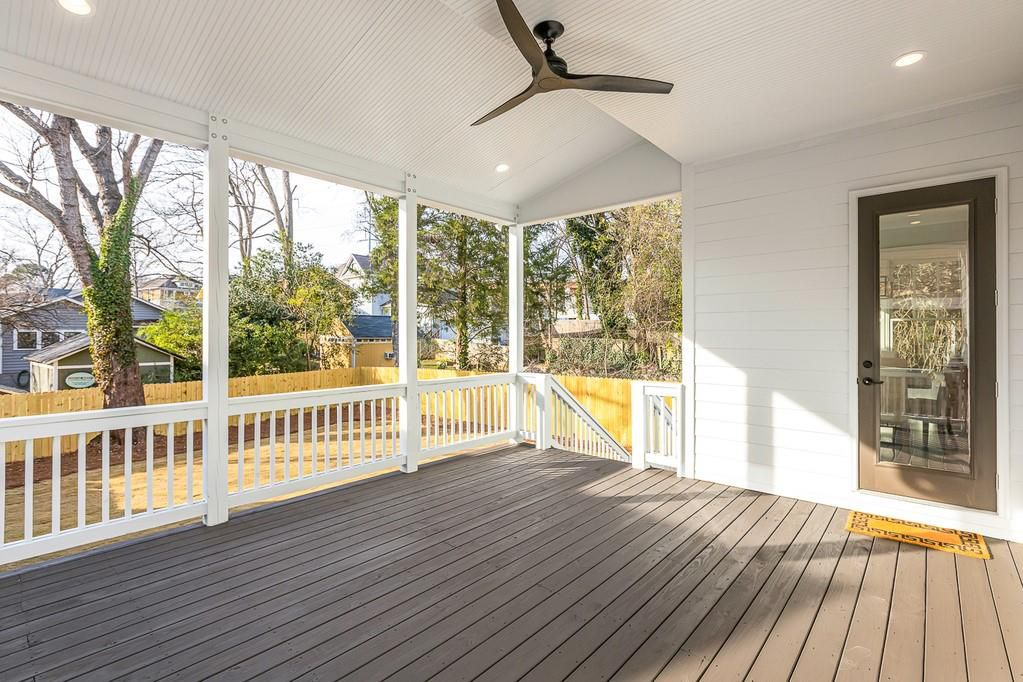 A deck with a ceiling fan overlooking a yellow grass yard.