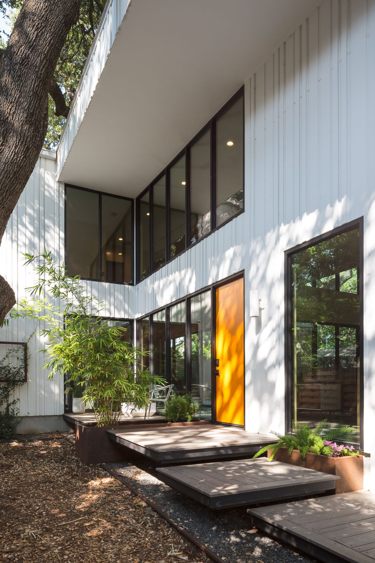 Two story contemporary with white walls and overhang, small front deck and goldenrod colored door