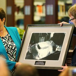 President Robin Linkhart of the Community of Christ is given a photo of the original printers manuscript as the LDS Church, in cooperation with the Community of Christ announces the release of the printers manuscript of the the Book of Mormon, during a press conference Tuesday, Aug. 4, 2015, at the LDS Church's History library in Salt Lake City.