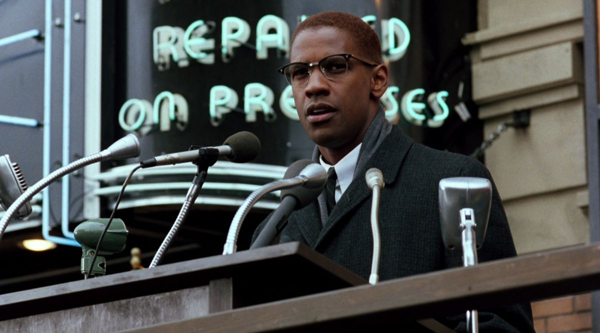 malcolm x stands at the podium outside and gives a speech
