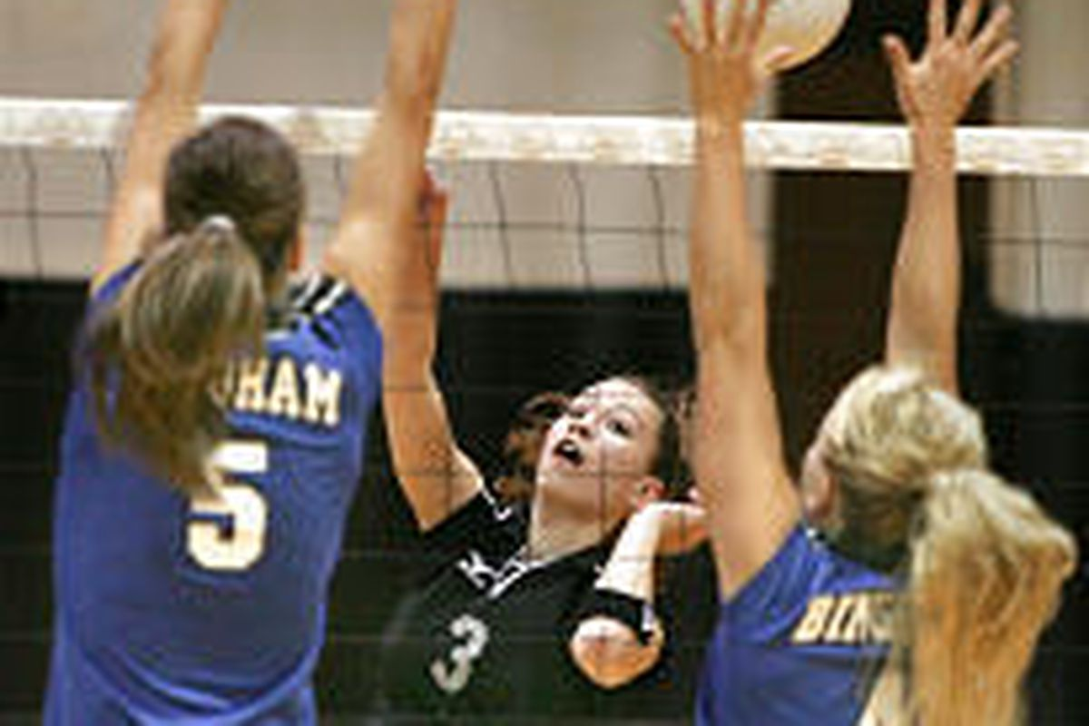 Alta's Bethany Carron (3) tries to hit past Bingham's Shelby Hansen (5) and Kelsie McCleary (4) during Tuesday 5A match at Alta High.