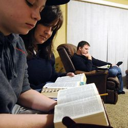 Kit Hunt, center, and her son Christian (13) follow along as Clayton, right, reads a passage from The Book of Mormon in their home in Bountiful on Thursday, Dec. 26, 2013.