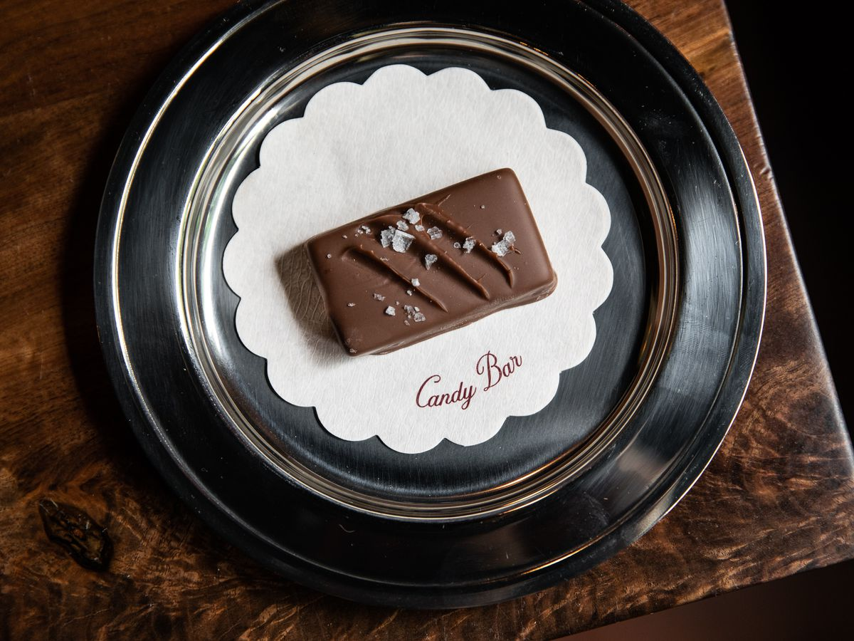 A chocolate bar with ripples on top and sea salt sits on a white Candy Bar paper coaster on a metal plate.