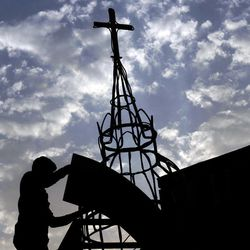 In this Thursday, Aug. 30, 2012 photo, a man works on a construction project at Sacred Heart Church in Manama, Bahrain. When Bahrain announced plans to build the largest Roman Catholic Church in the Gulf, it was accompanied by a noticeable dose of pride to showcase its traditions of religious tolerance. Instead, the planned church has turned into another point of tension in a country already being pulled apart by internal sectarian battles.