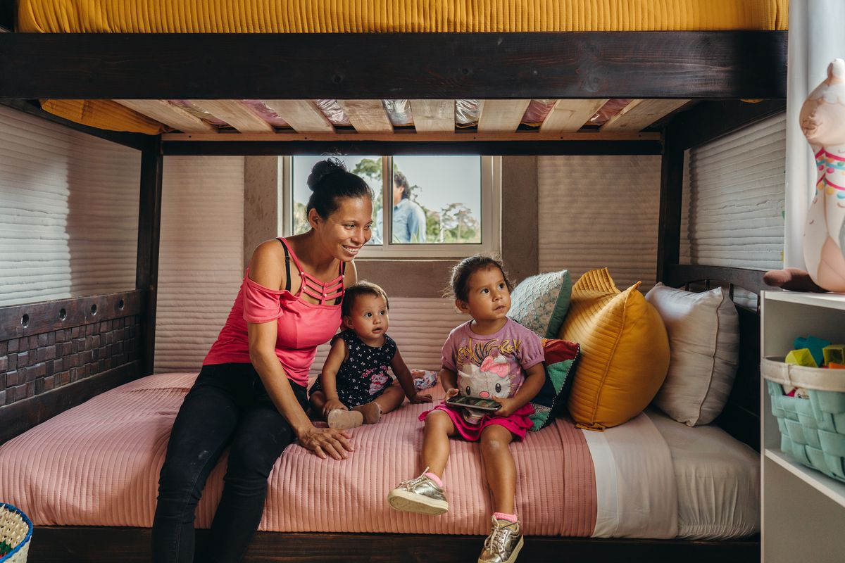 A woman and two small children sit on the bottom bed of a bunk bed.